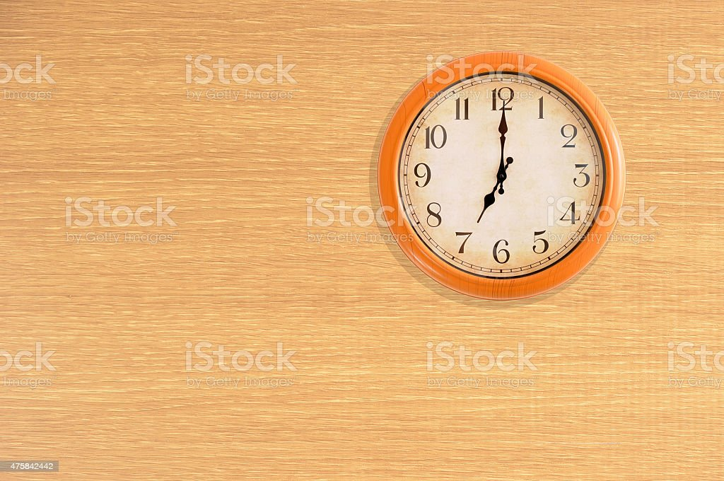 Clock showing 7 o'clock on a wooden wall stock photo
