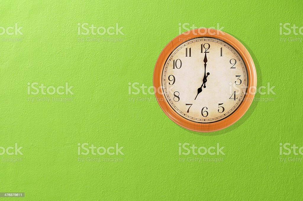 Clock showing 7:00 o'clock on a green wall royalty-free stock photo
