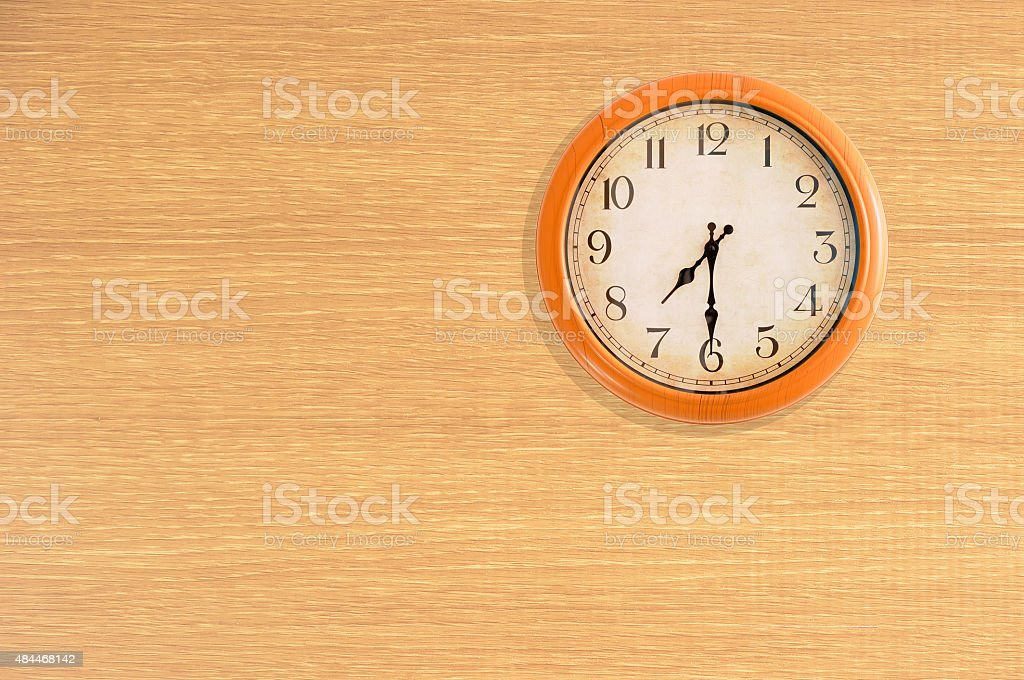 Clock showing 7:30 o'clock on a wooden wall stock photo