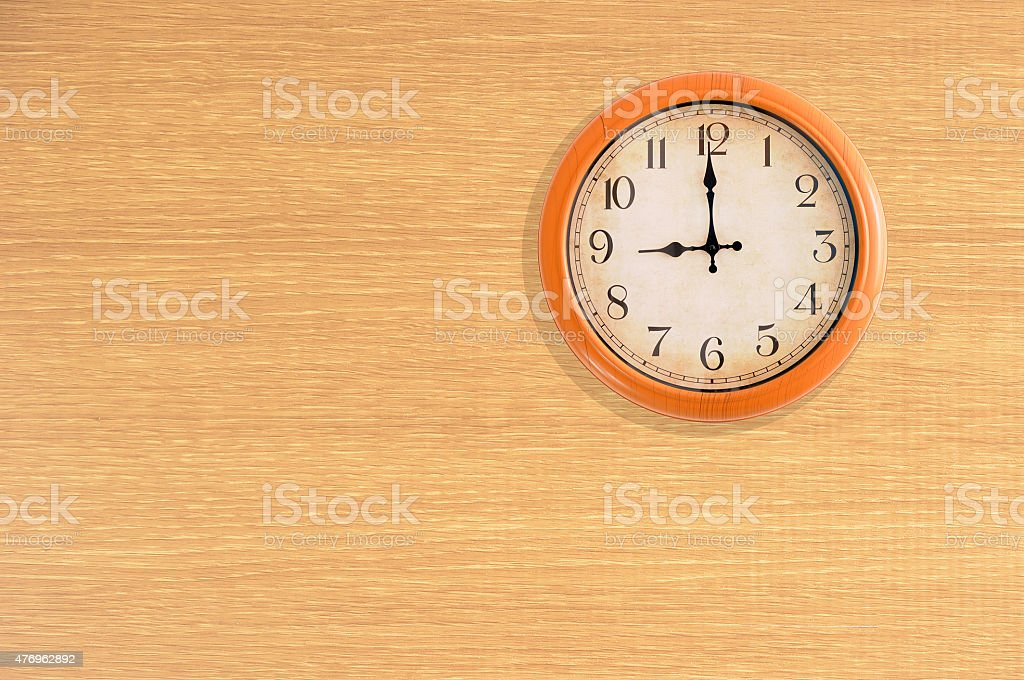 Clock showing 9 o'clock on a wooden wall stock photo