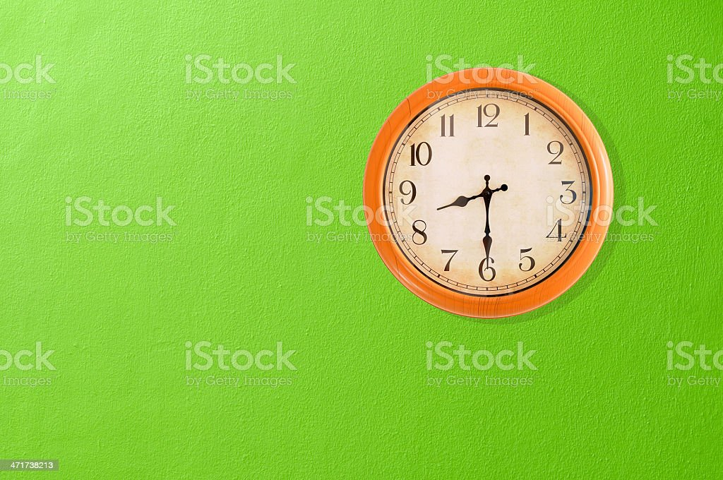 Clock showing on a green wall royalty-free stock photo