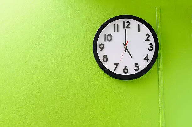 Clock signaling 5 o'clock hung on a lemon-green wall Clock showing 5 o'clock on a green wall  clock hand stock pictures, royalty-free photos & images