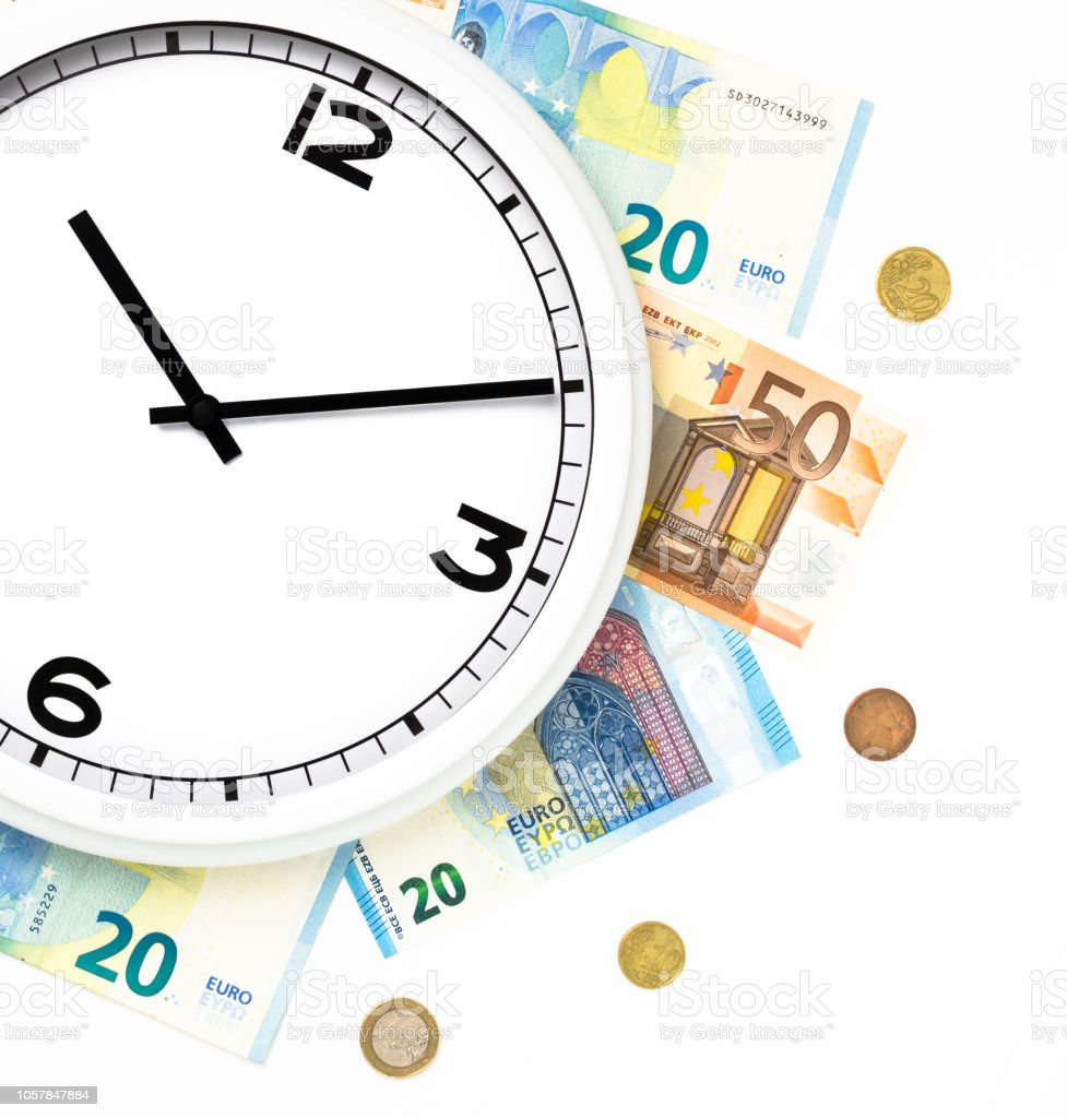 Clock surrounded by bills and euro coins stock photo