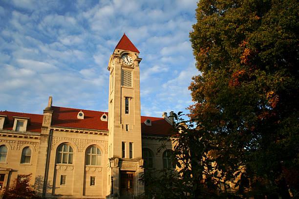 clock tower against a slightly cloudy blue sky - klokkentoren met luidende klokken stockfoto's en -beelden