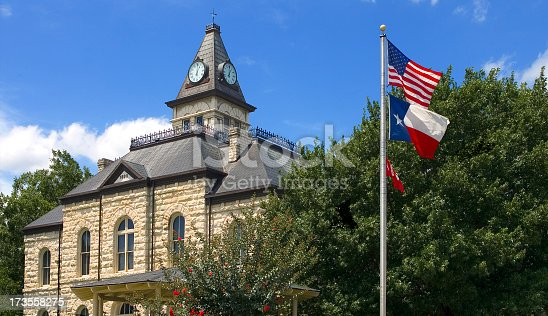 View of the Glen Rose, Texas Townsquare, Somerville County Courthouse in the background, US and Texas flags in foreground