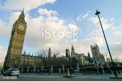 Clock tower of Big Ben in London UK with traffic passing by in the foreground during a beautiful autumn day. People are walking on the sidewalk across the street.