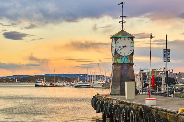 Clock tower on Aker Brygge Dock at the waterfront with marina on background Oslo, Norway: April 26 2017 - Clock tower on Aker Brygge Dock at the waterfront with marina on background. oslo stock pictures, royalty-free photos & images