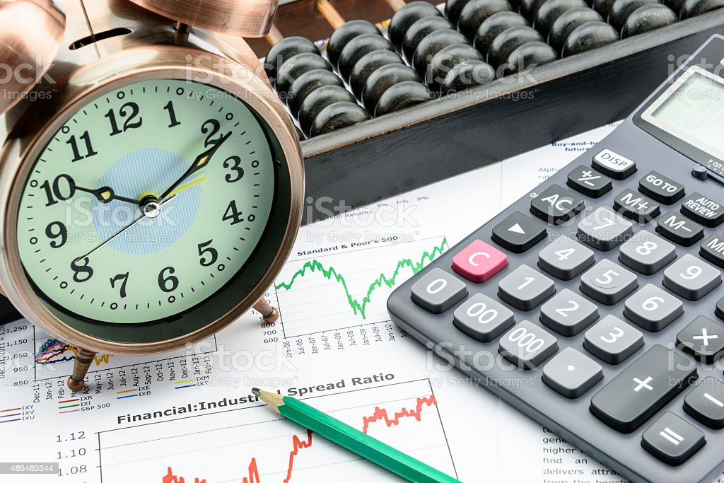 Clock with a calculator and an abacus on business reports. stock photo