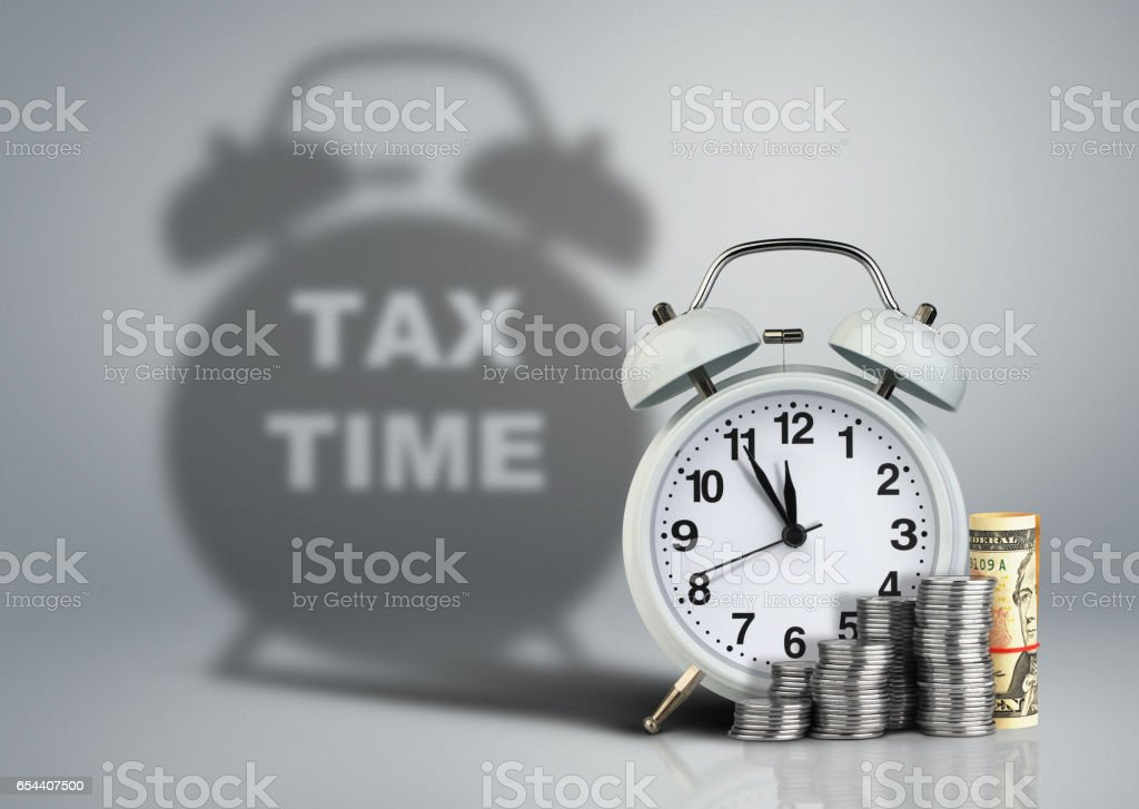 Clock with money and tax time shadow, financial concept stock photo