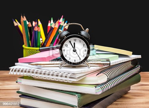 1045293630istockphoto Clock with pupil's supplies on the wooden table on blackboard background. Time to school. 996401512