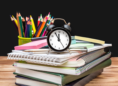 1045293630 istock photo Clock with pupil's supplies on the wooden table on blackboard background. Time to school. 996401512