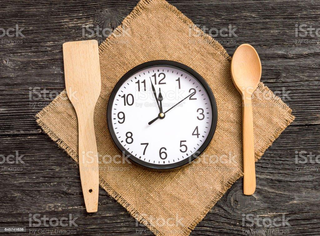 荒布を着たスプーン時計します。食事をする時間です。 ロイヤリティフリーストックフォト