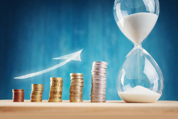 Clock with stacked coins and hourglass on blue background stock photo