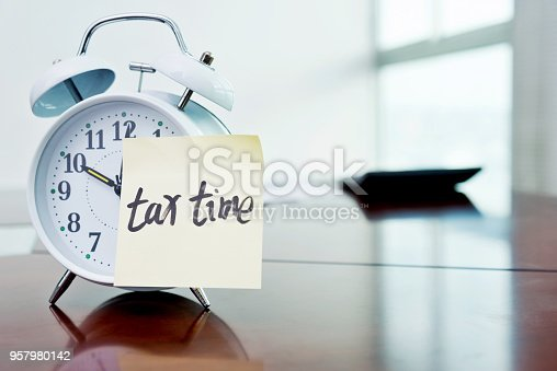 A clock with tax time sticky note and calculator on the desk.