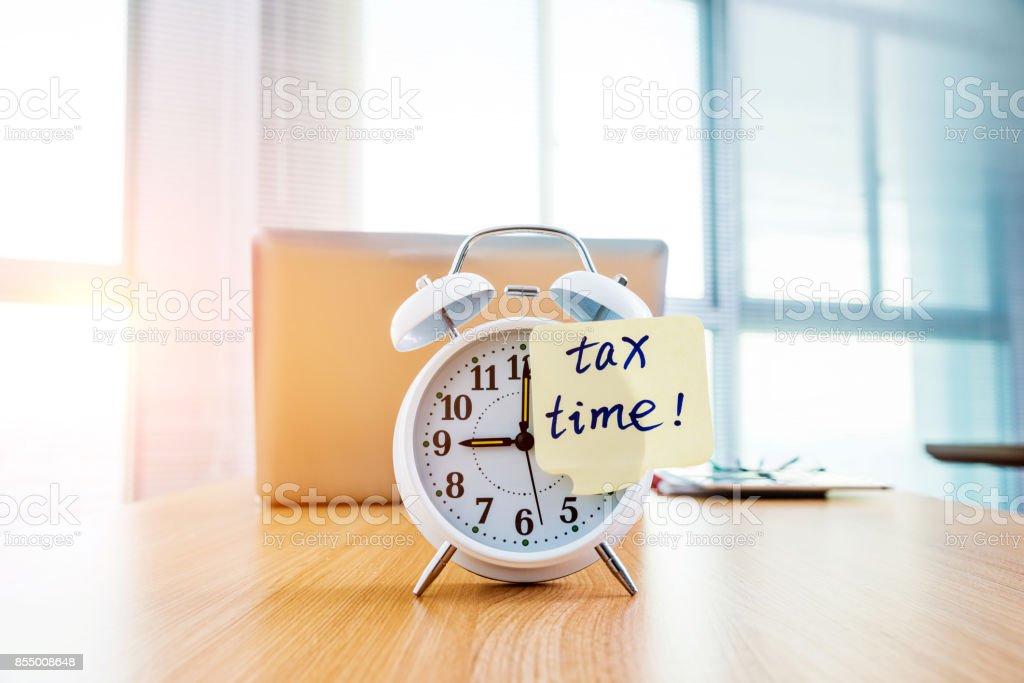 Eine Uhr mit Steuer mal Notiz am Bürotisch – Foto