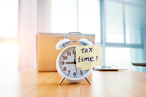 A Clock With Tax Time Sticky Note On Office Table - Fotografie stock e altre immagini di Affari