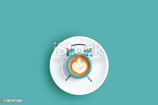 Alarm clock with the dial of cappuccino on turquoise background. Minimal styled coffee time concept.