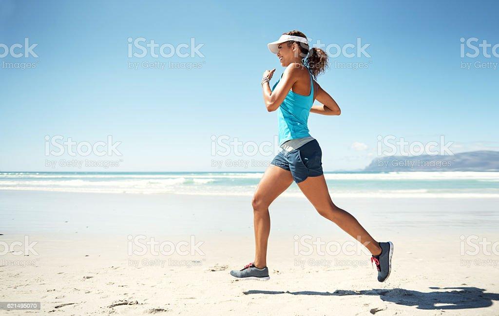Clocking some workout time alone the shore photo libre de droits