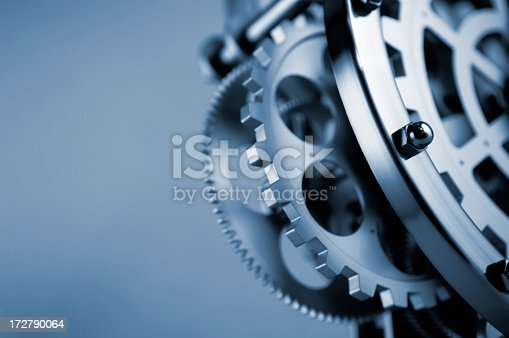 A blue tinted close up abstract image of gearwheels and cogs in part of a clockwork machine mechanism. The machine is against a plain background. Show with a selective focus with focus on the foreground. With copyspace.