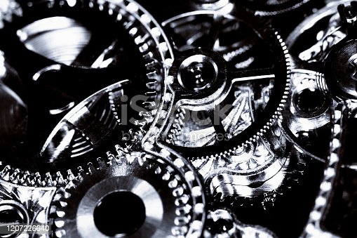 The intricately detailed cogs and wheels inside a watch or clock, here seen in black and white.