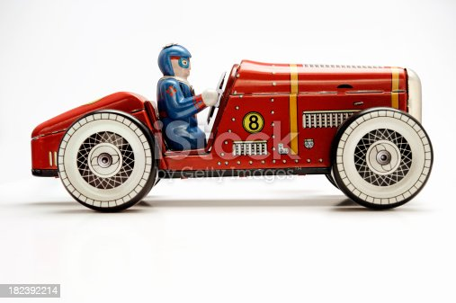 Vintage old red clockwork racecar made of tin isolated on white.