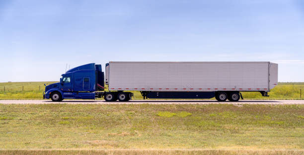 A Cloes-up View Of A Long Haul Semi Truck Speeding Down a Four Lane Highway stock photo