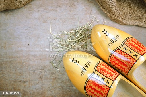 istock Clogs dutch Volendam, Amsterdam, Marken, wooden shoes at wooden background with hessian burlap and hay straw with copy space for your own text 1161139576