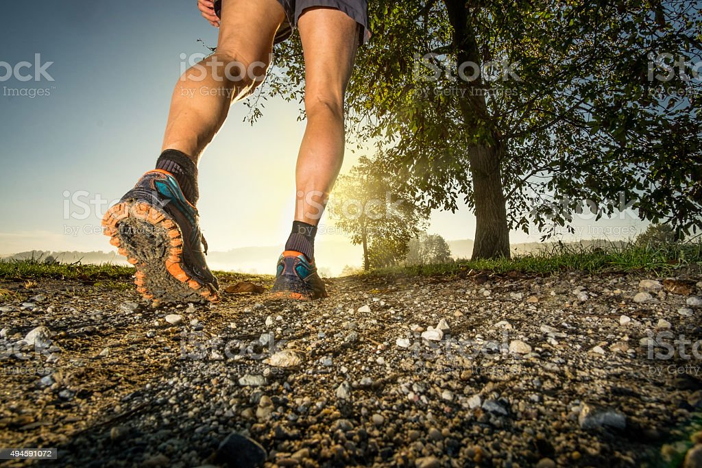 Clos up on shoes of man running in the countryside stock photo