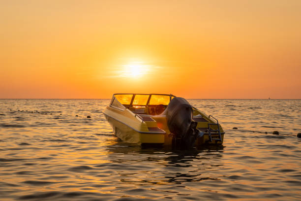 Close beautiful sea view of orange and yellow sunset with a moored motorboat against the horizon. stock photo