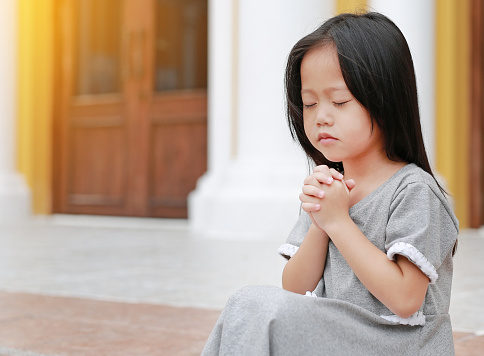 Close eyes little asian girl sitting and praying at the church.