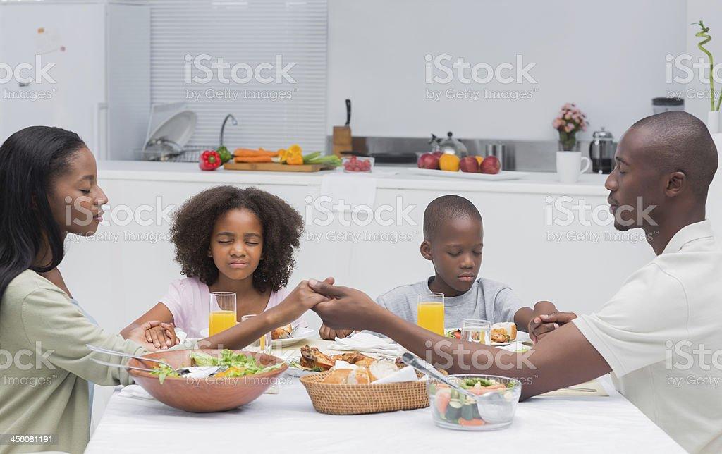 Close family saying grace before having dinner stock photo