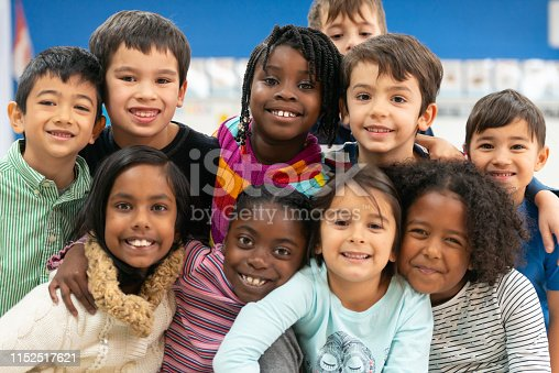 A group of diverse kids smile in this portrait. They are stacked on top of each other while cuddling in close and showing how happy they are.