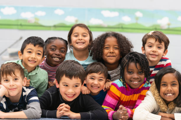 Close friends in class portrait A group of diverse kids smile in this portrait. They are stacked on top of each other while cuddling in close and showing how happy they are. primary school stock pictures, royalty-free photos & images