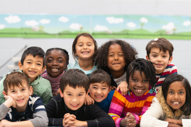 Close friends in class portrait A group of diverse kids smile in this portrait. They are stacked on top of each other while cuddling in close and showing how happy they are. children only stock pictures, royalty-free photos & images