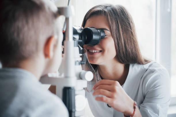 Enger Blick. Kleiner Junge, der seine Augen mit speziellen optischen Geräten durch einen weiblichen Arzt testen hat – Foto