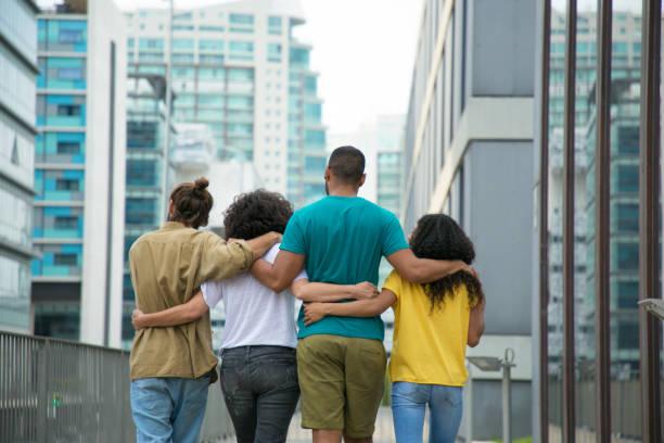 Schließen Sie männliche und weibliche Freunde, die die Stadtstraße entlanggehen – Foto