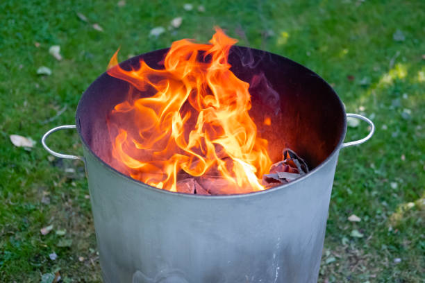 Close of a home made metal garden incinerator seen burning general household, non toxic water in a gardem setting. The heat reaches a very high temperature in the barrel due to heat being reflected from within the metal surface. dumpster fire stock pictures, royalty-free photos & images