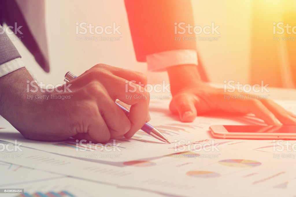 Close of hands of business men are working on a business report. stock photo