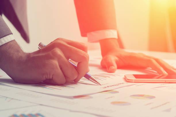 Fermeture des mains d'hommes d'affaires travaillent sur un rapport de l'entreprise. - Photo