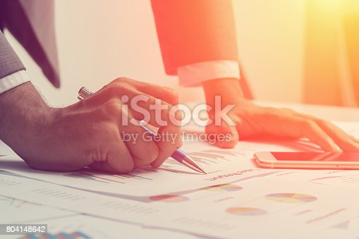 istock Close of hands of business men are working on a business report. 804148642