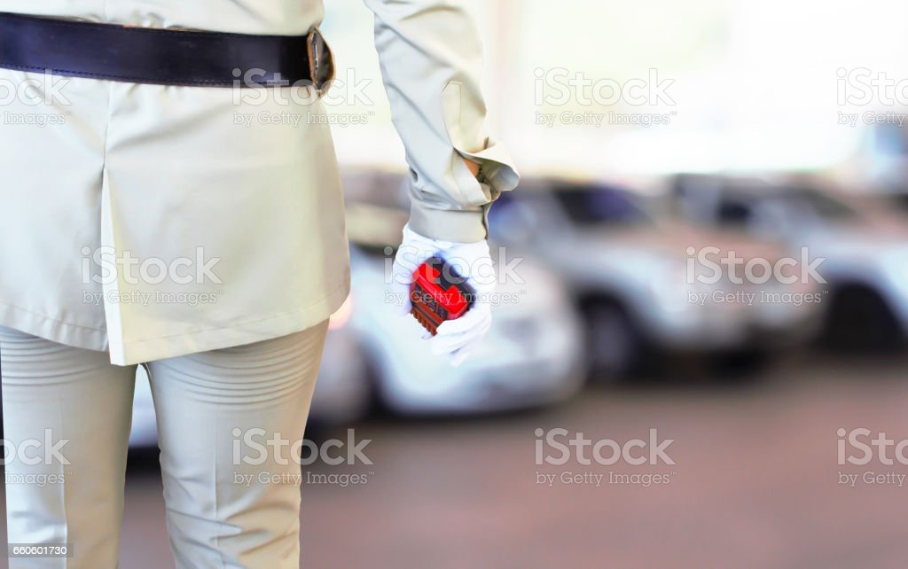 Close of of policewomen's hand on his transmitter. Security agent surveillance guard in park car blur background. royalty-free stock photo