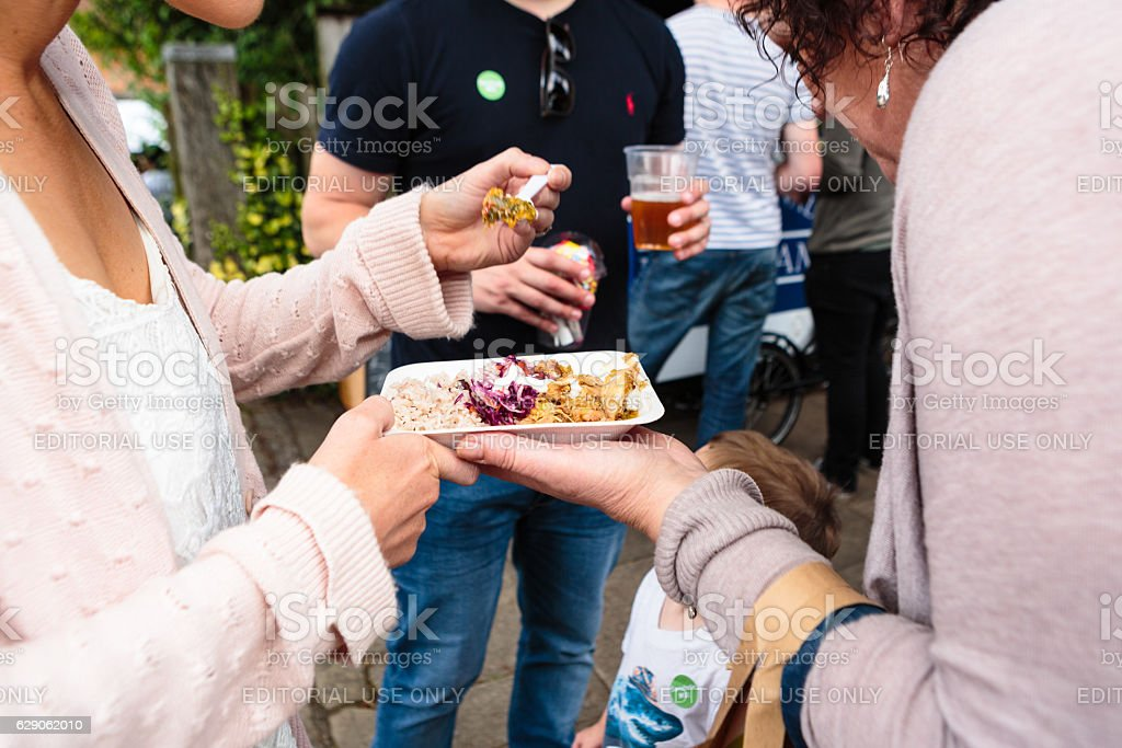 Close of of two women sharing food at a outdoor event stock photo