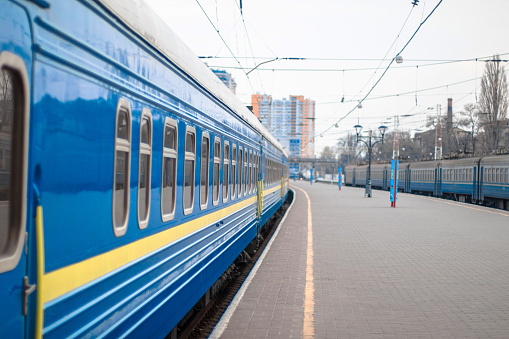 Close of the blue metal railway carriages with clean windows stand on the platform of the train station. Departure or arrival of a train. Travel concept