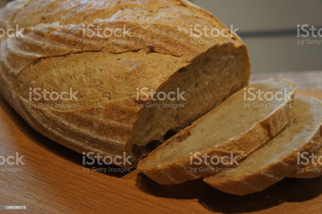 Close of up sliced home baked sourdough loaf of bread on a cutting board stock photo