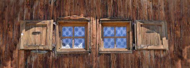 cerca de dos pequeñas ventanas en una fachada de madera de antiguo chalet alpino - foto de stock