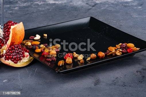 A close picture of a pomegranate on stone grey background, nuts in on the black plate. Symbol of New Year and Christmas