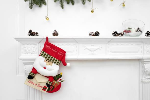 ein enger bild von schön dekorierten santa weihnachten socken mit ho! ho! ho! wort an einen kamin warten geschenke hängen - kamin weiß stock-fotos und bilder