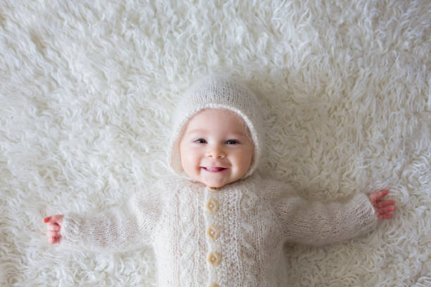 Close portrait of a little baby boy in white knitted onesie and a hat Close portrait of a little baby boy in white knitted onesie and a hat, smiling lying on back stock pictures, royalty-free photos & images