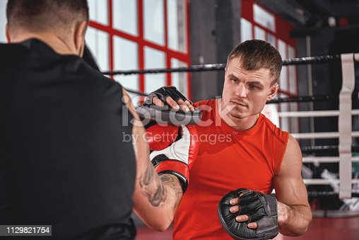 Training hard. Muscular athletic tattooed man in sports clothing training on boxing paws with partner opposite boxing ring