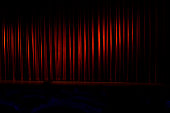 Theatrical stage is closed by red curtain.